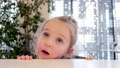 Thoughtful blonde little girl with pigtail leans on counter 76845736