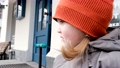 Anxious little girl in orange hat waits for mother by shop 76845737