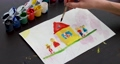 Child draws house and family picture with brush in gouache 76847764