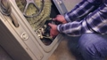 A specialist man takes out the electric motor from the washing machine. 76853484