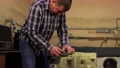 A man inserts a heating element into the drum of the washing machine. 76853485