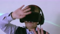 Boy in augmented reality headset looking at the camera moving his hands. 76854828