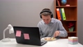 Young office worker, student, manager, wearing headphones, eating his lunch in his home office, during - a pandemic. With a computer in the foreground. 76856778