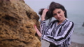 Freelancing. Girl stand near a cliff overlooking ocean with her hair blowing. 76856813