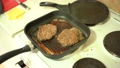 Burger patties are fried in a grill pan on the stove. 76872124