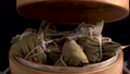 Taking zongzi from steamer, ready to eat rice dumpling for Dragon Boat (Duanwu) Festival with dark background. 76885506