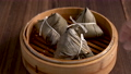 Taking zongzi from steamer, ready to eat rice dumpling for Dragon Boat (Duanwu) Festival with dark background. 76885507