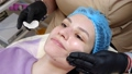 close-up, cosmetician in medical gloves applies evenly cosmetic cream or sunscreen to female face after peeling. skincare and sun protection concept. cosmetology on beauty salon 76887003