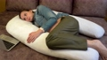 Pregnant girl lying on the pregnancy pillow and working with a laptop computer. 76890418
