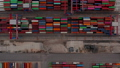 Overhead birds eye aerial view of colorful cargo containers and industrial cranes arranged in rows in a port 76896503