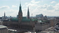 Aerial view of Hamburg city hall with green roof surrounded by traditional old buildings in city center 76897795