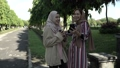 Muslim women in hijabs outdoors on sunny day with friend happy 76918559
