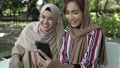muslim woman in head scarf meet friends and using phone in the park 76918573
