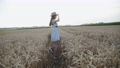 Happy carefree girl walks among golden wheat and poses to camera 76949380