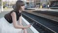 Thoughtful girl uses phone on railway platform 76949383