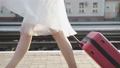 View of girl's stepping with suitcase on platform with smile on face 76949384