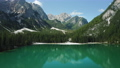Aerial footage over lake Braies, Pragser Wildsee and mountains, in the background, on a sunny bright summer day, in Dolomites, Italy 76953572