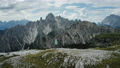 Aerial view of women hiking close to Auronzo di Cadore of Cadini di Misurina mountains group in Dolomites, Italy, part of Tre Cime di Levaredo national park and UNESCO world heritage site. 76953574