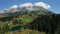 Women on top of hill with uprooted pine trees after strong wind in Lake Carezza - most beautiful lakes in South Tyrol, Dolomites. Circle drone motion 76955939