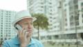 Man in a hat talking on a mobile phone while standing on the background of buildings 76959661