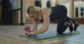 The active beautiful girl in sport clothes doing plank exercise for calorie burning and strengthens spine. Young woman practice workout in gym or fitness club. 76982350
