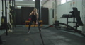 Sport woman doing battle ropes exercise at gym. Fitness girl athlete with fit body exercising, doing functional training with heavy ropes indoors. Rope workout. 76982359