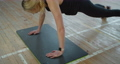Athletic woman with smart watch does push-ups as part of her cross fitness. Muscular athlete woman in the gym. Sporty woman girl. 76982712