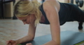 Beautiful sport woman doing plank workout at a gym to improve her abs. Fitness girl fit workout in gym working her core muscles. 76982715