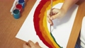 The rainbow is symbolically drawn by children's hands in close-up with paints 76985633