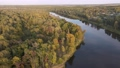 Aerial view of woodland and calm river at sunset. 76985642