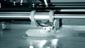 3d printer prints orange object close-up. Automatic three dimensional 3D printer 76999686