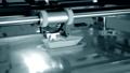 3d printer prints orange object close-up. Automatic three dimensional 3D printer 76999688
