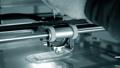 3d printer prints orange object close-up. Automatic three dimensional 3D printer 76999693