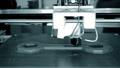 3d printer prints blue object close-up. Automatic three dimensional 3D printer 76999696