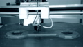 3D printer works and creates an object from hot molten plastic close-up. 76999697