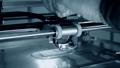 3d printer prints orange object close-up. Automatic three dimensional 3D printer 76999698