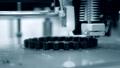 3d printer prints black object close-up. Automatic three dimensional 3D printer 76999701