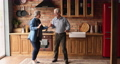 Overjoyed older senior couple dancing in kitchen. 77003543