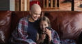 Happy woman with cancer remission using smartphone with kid. 77003550