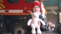 Little girl holding a toy standing in a fire guard station 77007385