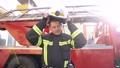 Fireman putting off helmet after work standing near a truck 77007400