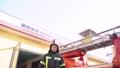 Fireman putting off helmet after work standing near a truck 77007402