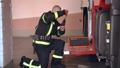 Fireman in equipment prepare special kit with tools at fire truck 77007403