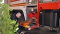 Fireman in equipment prepare special kit with tools at fire truck 77007406