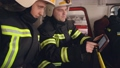 Two firemen analysing data looking on digital tablet in the truck cabin 77007416