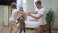 Happy father having fun with daughters dancing in slow motion as cheerful mother taking video on smartphone at background. Joyful relaxed Caucasian family enjoying weekend together at home 77010547