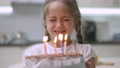 Close-up of charming little girl with closed eyes making wish and blowing candles on birthday cake. Portrait of happy Caucasian pretty child celebrating birthday indoors at home. Joy and lifestyle 77010572