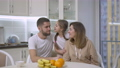 Happy Caucasian daughter kissing and hugging parents looking at camera and smiling. Portrait of joyful relaxed family enjoying leisure on weekend together at home. Joy and lifestyle 77010573