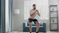 Active sportsman steps in half squat with elastic belt 77019758