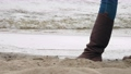 walking by the sea in winter. close-up. woman traveller, in brown boots, is walking along sandy beach by the sea or river, on windy, cold, winter day. walk along the beach in winter 77024339